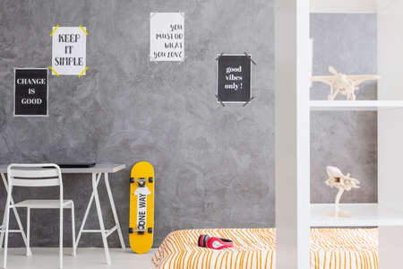 Ruime jongen slaapkamer met een werkplek en skateboard op basis van de cyaan muur