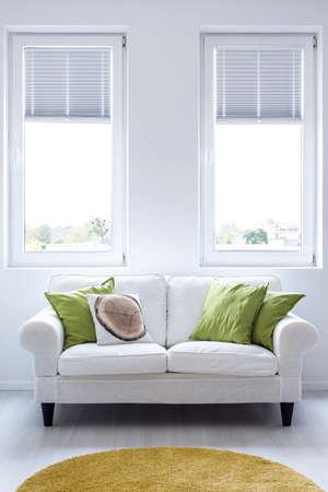 2 つのウィンドウを持つ白い壁バック グラウンドのクッションを備えたエレガントなソファ