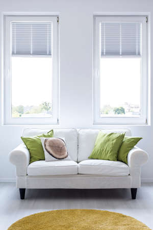 Elegant couch with cushions on a white wall background with two windows Фото со стока