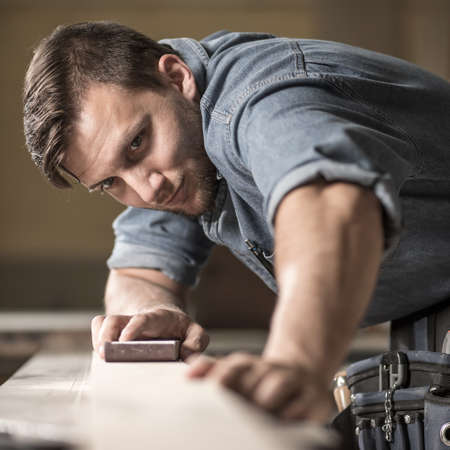 skilled: Image of young skilled joiner polishing wooden board