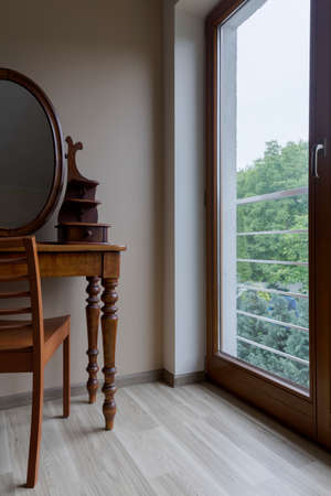 dressing table: Room corner with parquet, wooden chair, elegant dressing table with a mirror and the window with the view of a garden Stock Photo