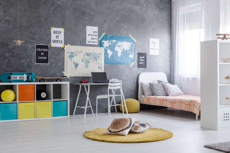 Bright, spacious room with bed, desk, colourful boxes and posters on the wall