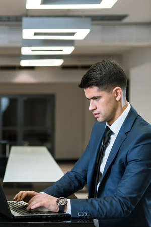 professionalist: Elegant businessman with the laptop, concentrated on his work Stock Photo