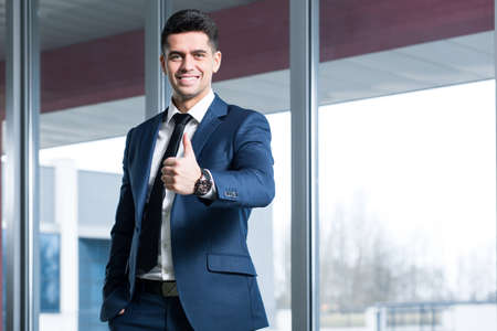influential: Elegant, smiled man in suit standing in open space area with his thumb up