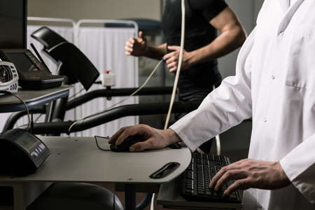 stress test: Closeup of a doctor supervising examination of a sportsman on the computer screen