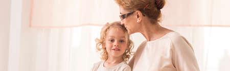 tenderly: Grandmother tenderly kisses the head of his little grandson Stock Photo
