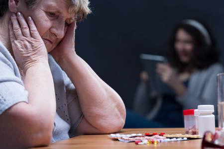 persona deprimida: Mujer en la depresión stearing en las pastillas situadas sobre una mesa Foto de archivo