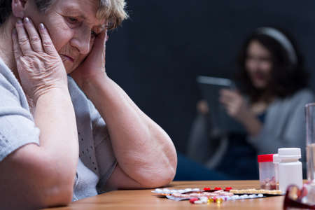 depressed person: Woman in depression stearing at the pills located on a tabletop