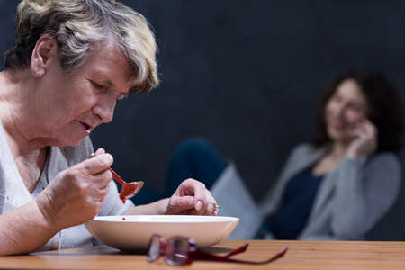 lack of water: Elder woman eating soup with young girl taking on the phone behind her Stock Photo