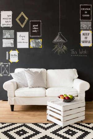 #63930335   Modern Gestaltete Innenraum Mit Einer Schwarzen Wand Mit  Motivplakate Auf, Weißen Couch Mit Kissen, Couchtisch Aus Der Holzkiste Und  Teppich Aus
