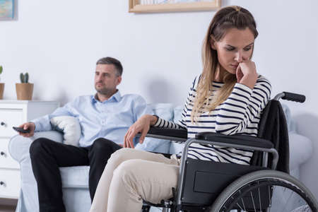 woman alone: Sad woman sitting on a wheelchair, in the background her husband sitting on a sofa Stock Photo
