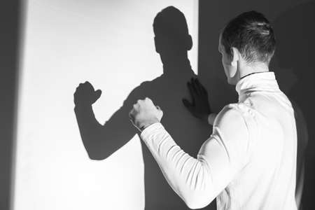 shadow man: Young man demonstrating his muscles to his shadow on the wall Stock Photo
