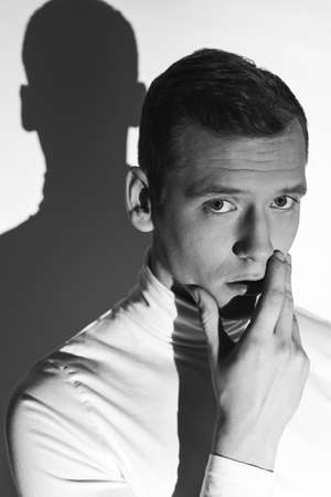 lunacy: Thoughtful man in white polo neck with his hand on a chin