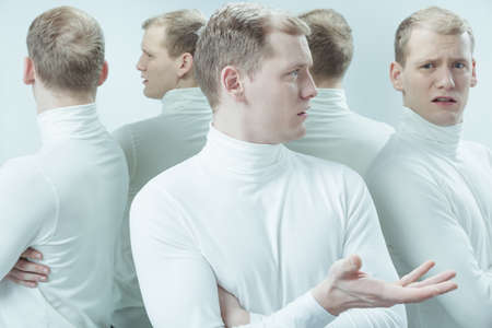 lunacy: Man talking with his mirror reflection with his arms folded Stock Photo