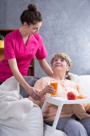 home keeping: Nurse helping in daily activities and eating the meals Stock Photo