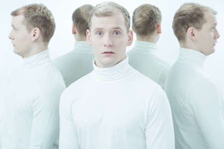 lunacy: Surprised man in white polo neck, surrounded by his reflections Stock Photo