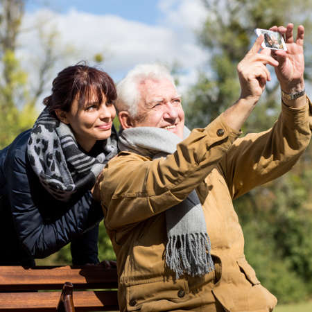 Image of elderly man taking photo with his granddaughter Stock Photo