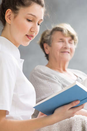 Young woman reading a book to elder woman Stock Photo