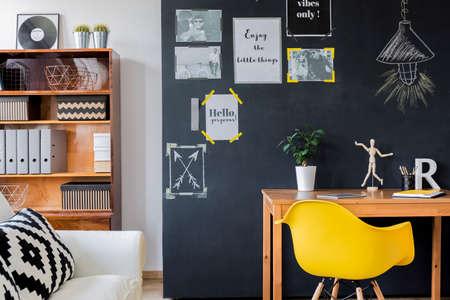 동기식 포스터가 달린 검은 색 벽이있는 현대적인 디자인의 객실로 나무 책상, 미니멀 한 노란색 의자, 바인더가 달린 랙 및 쿠션이있는 흰색 소파