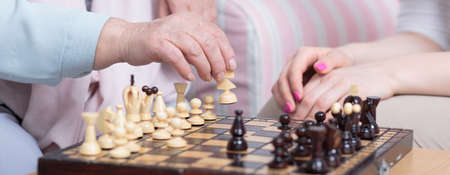 close shot: Close shot of a chess board played by senior woman and her granddaughter Stock Photo