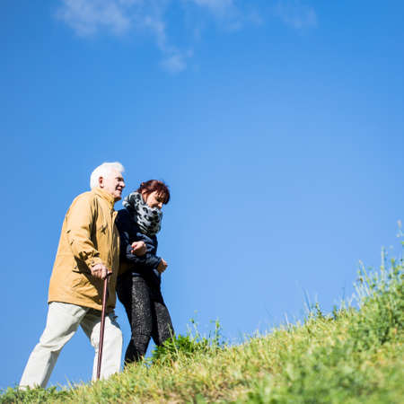 elderly woman: Senior man with cane walking in the mountians