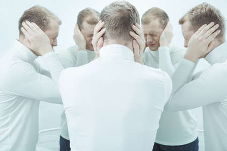 lunacy: Mans mirror reflections covering ears by hands refuge to noise Stock Photo