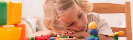 grandkids: Sad and bored boy rests his head on a table full of toys Stock Photo