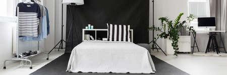 Intérieur de la chambre lumineuse avec grand lit, support minimaliste pour les vêtements et le bureau à domicile