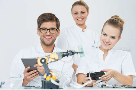 man at work: Shot of three happy engineers looking at a robot Stock Photo