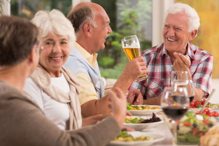 Shot of a group of elderly people having a dinner party in a house
