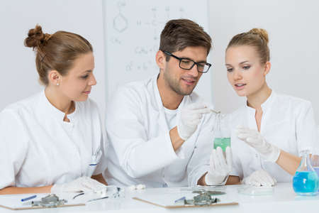 technical university: Shot of three young chemists working in their lab