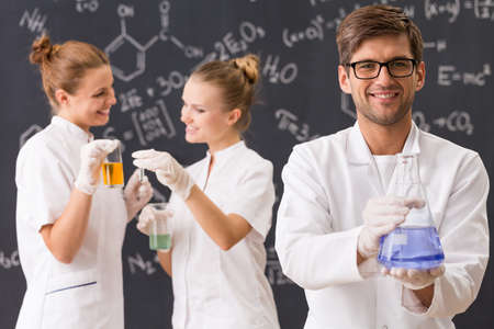 technical university: Shot of three happy chemists standing against a blackboard wall