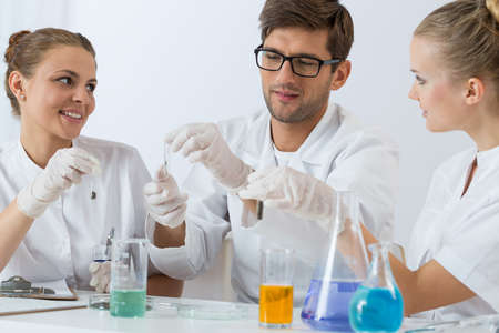 technical university: Shot of three young smiling chemists carrying out an experiment Stock Photo