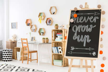 Part of a child room with a blackboard on a rack, desk with chair and bookstand made with boxes Zdjęcie Seryjne