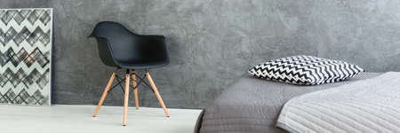Modern design of grey spacious bedroom with comfortable bed. By the wall black chair