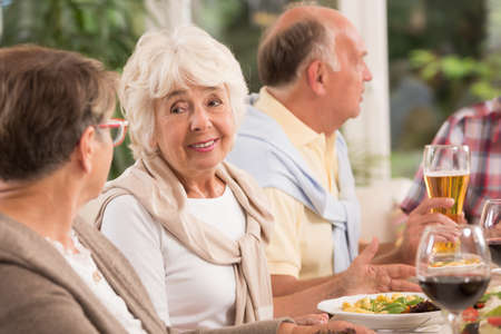 dinner party: Shot of a group of elderly people talking at a dinner party