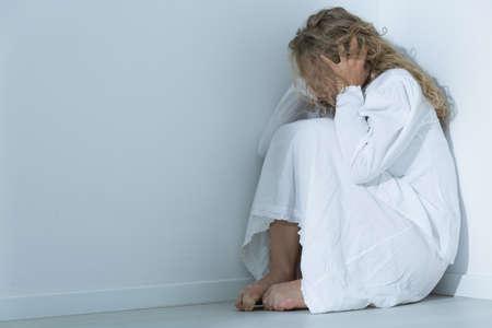 Captura de una mujer joven loco sentado en un rincón de una habitación blanca Foto de archivo - 62859011