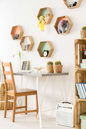 Part of a bright child room with wooden chair and boxes and desk