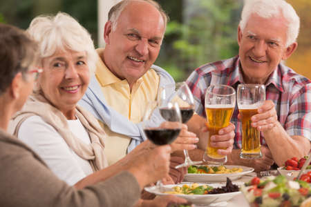 Shot of a group of elderly people proposing a toast at a dinner party