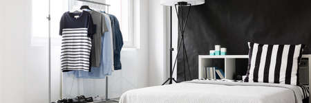 Well-lighted room corner with minimalistic clothes rack and bed at the black wall background Banque d'images