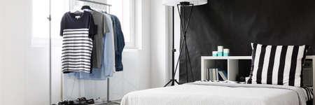 Coin de la pièce bien éclairé avec support de vêtements minimaliste et lit sur le fond de mur noir