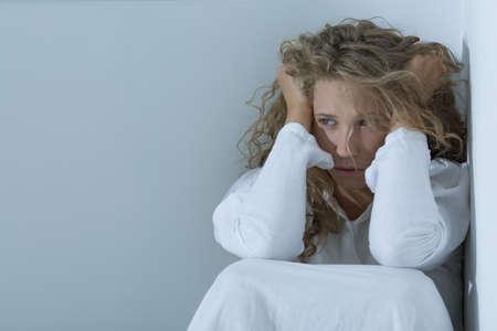 Shot van een trieste jonge vrouw zitten in een witte ruimte en houdt haar hoofd