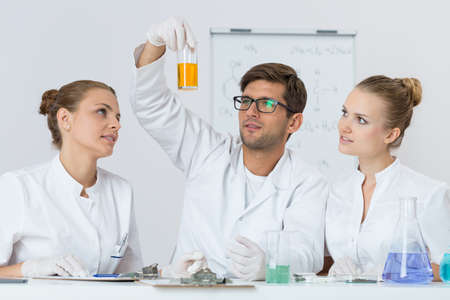 technical university: Shot of three young chemists waiting for the results of their experiment