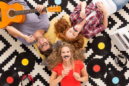 Bovenaanzicht van gelukkige vrienden met grappige foto props liggend op een patroon achtergrond Stockfoto