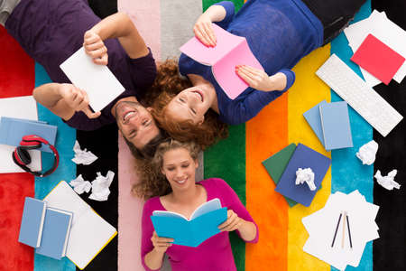 Top view of three happy students reading their notes before a test, colorful background