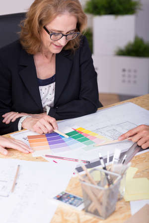 paint samples: Mature woman looking at paint samples at the table
