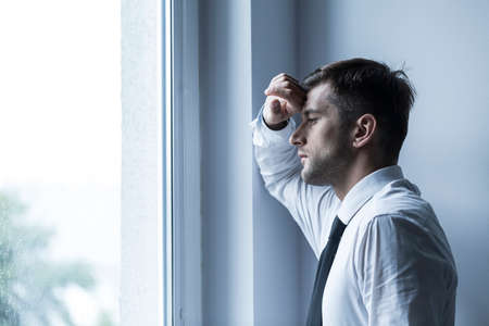 homme triste: Shot of a sad businessman looking through the window