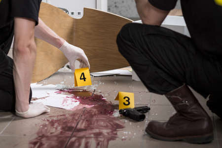 gun room: Two police officers at the scene looks at the traces of blood Stock Photo