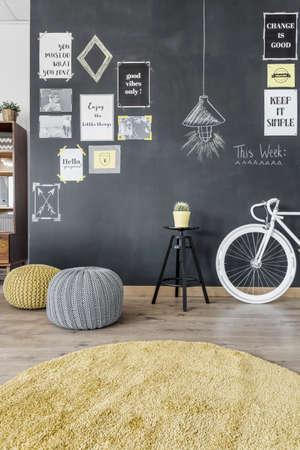 Plan d'une petite pièce avec un vélo, des poufs et un tableau noir avec des affiches et des photos dessus