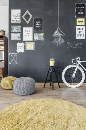 interior decor: Shot of a small room with a bike, pouffs and a blackboard wall with posters and pictures on it